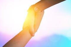 Руки крупного плана используемые для того чтобы помочь одину другого на предпосылке против как крюка hang долларов принципиальной Стоковая Фотография
