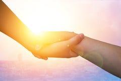 Руки крупного плана используемые для того чтобы помочь одину другого на предпосылке против как крюка hang долларов принципиальной Стоковое фото RF