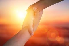 Руки крупного плана используемые для того чтобы помочь одину другого на предпосылке против как крюка hang долларов принципиальной Стоковые Фотографии RF