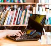 Руки крупного плана печатая на тетради в библиотеке Стоковое Изображение RF
