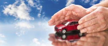 Руки кладя защитно вокруг автомобиля стоковая фотография