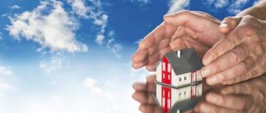 Руки кладя защитно вокруг дома стоковое изображение