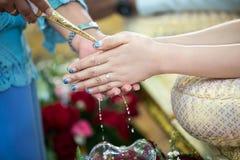 Руки лить благословение мочат в диапазоны ` s невесты Стоковое Фото