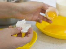Руки ломают сырцовое яичко Разъединение белизны яичка от желтка Стоковые Фотографии RF