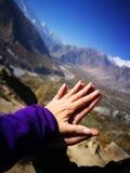 Руки любовника касаясь и togethering с предпосылкой горы и голубого неба для концепции любов и излечивать стоковая фотография rf