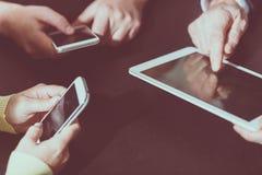 Руки людей используя мобильные телефоны и цифровую таблетку стоковое фото rf