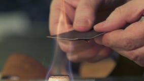 Руки людей на процессе огня кожа для того чтобы сделать кожаный пояс акции видеоматериалы