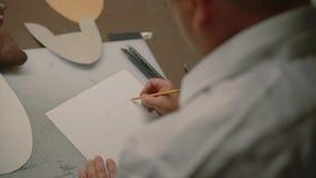 Руки людей рисуют карандаш на бумаге сток-видео