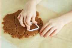 Руки маленького ребенка подготавливают тесто, пекут печенья в кухне Близкая поднимающая вверх концепция leasure семьи стоковая фотография rf