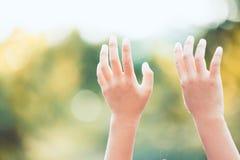 Руки маленького ребенка поднятые вверх Стоковые Фото