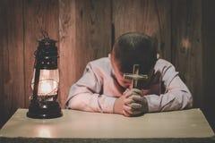 Руки мальчика держа святой крест и моля к богу, ребенку моля для вероисповедания бога стоковая фотография rf