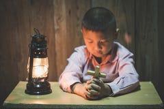 Руки мальчика держа святой крест моля к богу в темноте и с лампой рядом с, ребенок моля для вероисповедания бога стоковое фото rf