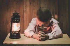 Руки мальчика держа святой крест моля к богу в темноте и с лампой рядом с, ребенок моля для вероисповедания бога стоковая фотография rf
