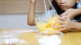 Руки мамы и ребенка подготавливающ и аранжирующ тесто печенья перед процессом выпечки сток-видео
