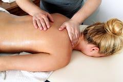 Руки массажируя женские плечо и заднюю часть Стоковые Фото