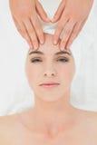 Руки массажируя лоб женщины на курорте красоты Стоковые Фотографии RF