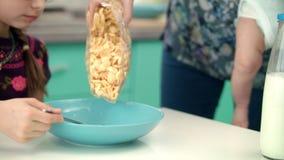 Руки матери лить хлопья мозоли в голубой шар Подготовка завтрака для ребенка акции видеоматериалы