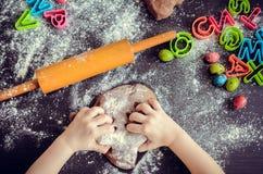 Руки маленькой девочки замешивая тесто Стоковые Фото