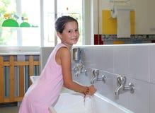 Руки маленькой девочки моя в керамической раковине в ванной комнате o Стоковое Изображение RF