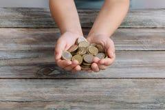 Руки мальчика держа монетки денег стоковое изображение