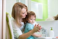 Руки мальчика ребенка моя с мылом в ванной комнате стоковое фото