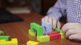 Руки мальчика собирают дизайнера, кубов строения сток-видео