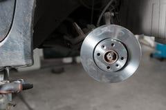 Руки механика автомобиля заменяют тормозы в гараже Стоковое фото RF