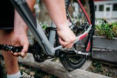 Руки механика велосипеда регулируют задействуя педали Стоковые Фотографии RF