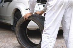 Руки механика в белой равномерной держа автошине на предпосылке гаража ремонта Концепция обслуживания автомобиля Стоковая Фотография