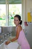 Руки милой маленькой девочки моя в керамической раковине в ванне Стоковая Фотография RF