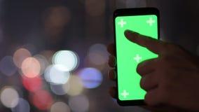 Руки молодого человека используя телефон против взгляда города вечером сток-видео