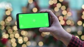 Руки молодого человека используя телефон против загоренных рождественских елок outdoors сток-видео