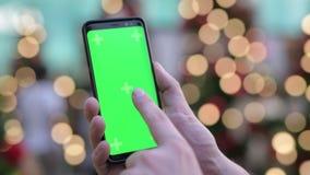 Руки молодого человека используя телефон против загоренных рождественских елок outdoors акции видеоматериалы