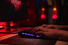 Руки молодого gamer укомплектовывают личным составом терять пока играющ видеоигры на com стоковые изображения rf