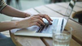 Руки молодой женщины используя сенсорную панель и печатающ outdoors видеоматериал