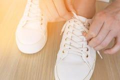 Руки молодой женщины связывая шнурки на белых тапках, конце-вверх Солнечное изображение стоковая фотография rf