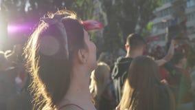 Руки молодой красивой женщины поднимаясь и веселить вверх на улице во время фестиваля, счастливого, толпе вентиляторов стоя вокру акции видеоматериалы
