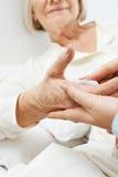 Руки моя прикованную к постели старшую женщину Стоковое Фото