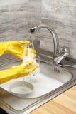 Руки моя стекло под проточной водой против кухонной раковины Стоковое Фото