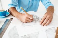Руки молодого бизнесмена сидя на таблице с портретом чертежа карандаша Белая современная предпосылка интерьера офиса Стоковая Фотография