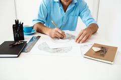 Руки молодого бизнесмена сидя на таблице с портретом чертежа карандаша Белая современная предпосылка интерьера офиса Стоковое фото RF