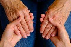 Руки молодой женщины держа руки пожилой женщины Стоковое Изображение