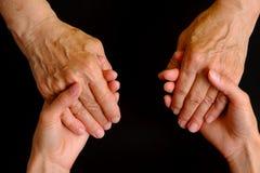 Руки молодой женщины держа руки пожилой женщины Стоковые Изображения