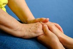 Руки молодой женщины держа руки пожилой женщины Стоковая Фотография RF
