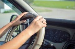 Руки молодой женщины держа рулевое колесо внутрь стоковые фото