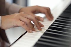 Руки молодой женщины играя рояль Стоковая Фотография