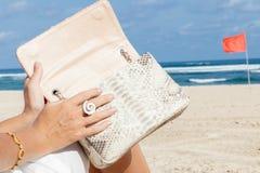 Руки молодой женщины конца-вверх с роскошной дорогой сумкой питона snakeskin Индийский океан на предпосылке bali Индонесия Стоковые Фотографии RF