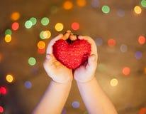 Руки младенца держа сердце Стоковые Изображения RF