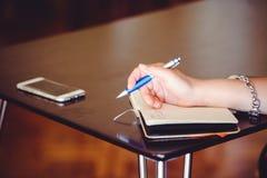 Руки написаны в тетради Стоковое Изображение