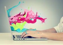 Руки на клавиатуре с красочным брызгают из монитора Стоковая Фотография RF